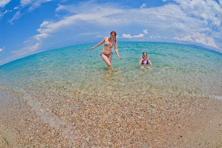 Matka a dcera se těší čas na tropické pláži Reklamní fotografie - 33132288