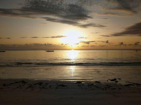 Romantic, extraordinary sunset in Jambiani on Zanzibar by the sea with horizon and fishing boat Banco de Imagens