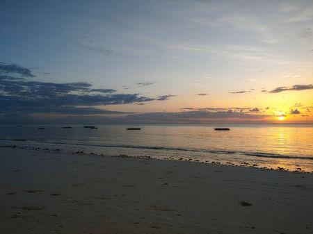 Romantic, extraordinary sunset in Jambiani on Zanzibar by the sea with horizon Banco de Imagens