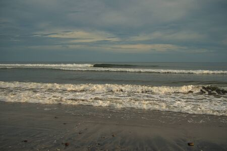 Just before a romantic sunset on the deserted beach in Panama on the Caribbean side, sea with waves