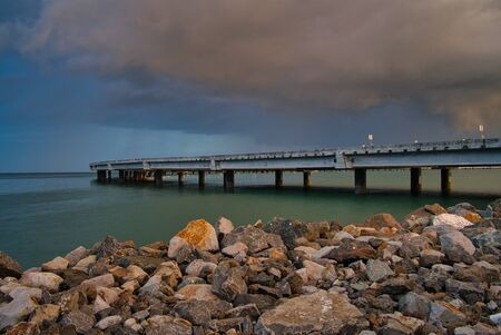 A deserted bridge over the sea in Panama, stones in the foreground and purple clouds, just before a thunderstorm Stock fotó