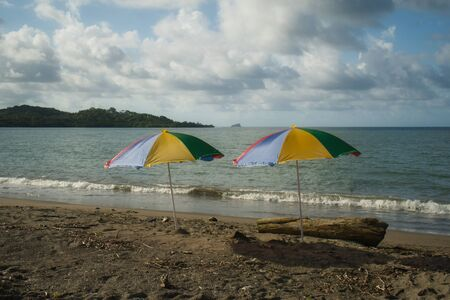 Different facets of lonely stands in Panama with palm trees, parasol