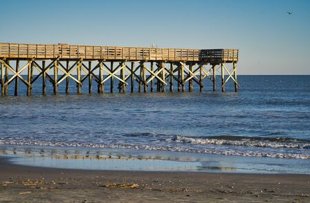 Fishing pier, wooden pier that protrudes over the sea into the water with a cloudless sky Standard-Bild