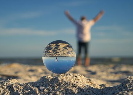 Man with arms outstretched is cheerful and happy on the beach at Sanibel Island, photographed through a glass ball