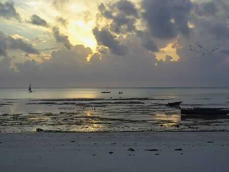 Sunrise, sunset with dream scenery and wanderlust on the lonely beach on Zanzibar, fishing boats and horizon in the background