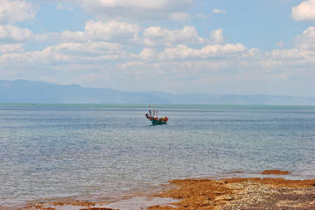 Asian fishing boat in a bay in shallow water off the coast of Cambodia