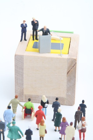 thumbnail: miniature figurines of a politician speaking to the people during an election rally