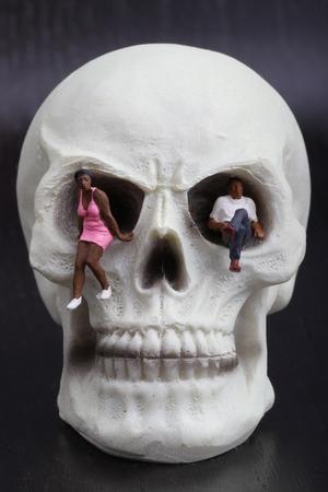 miniature figurines of depressed people sitting on a skull