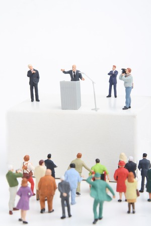 miniature figurines of a politician speaking to the people during an election rally