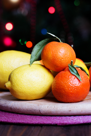 tangerines and lemons on background of Christmas tree. mixed of fresh fruits with leaves. Rustic still life arrangement with citrus.