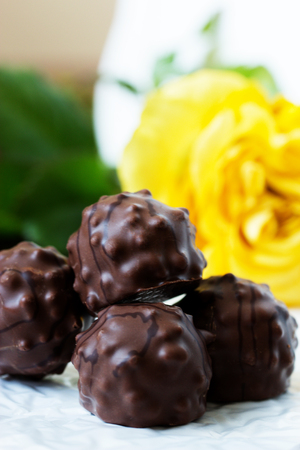 chocolates with nuts. chocolate candy on background with yellow roses Stock Photo