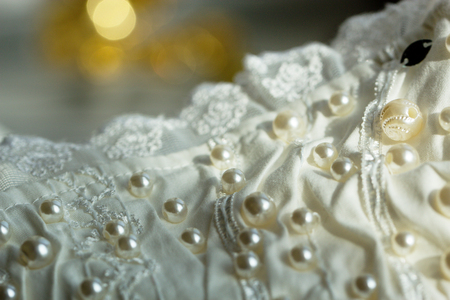 satin dress: textile wedding background with beads. Tiny pearls embroidered over a wedding dress