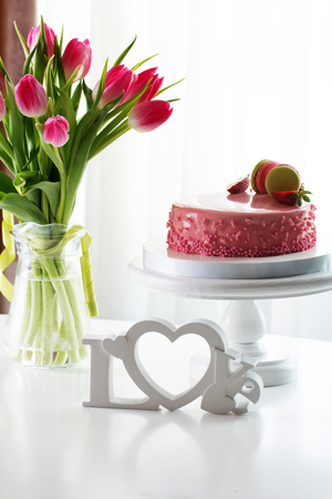strawberies: Pink romantic cake decorated with macaroons and strawberry. Delicious creamy cake with strawberies and macaroons on table closeup