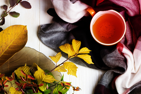 autumn picture with yellow, red and orange leaves, a cup of tea, a scarf. Cup of tea and autumn leaves on a white wooden table