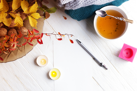 Autumn flatlay on wooden backdrop with a cup of tea and  fallen dry yellow and red leaves. Free space for text. Cozy home concept Zdjęcie Seryjne