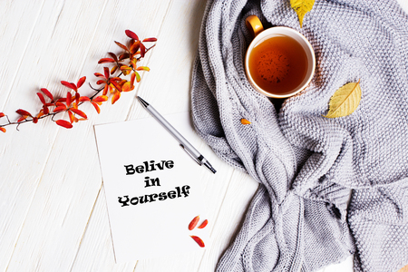 Autumn flatlay on wooden backdrop with a cup of tea and  fallen dry yellow and red leaves. Believe in yourself. Cozy home concept