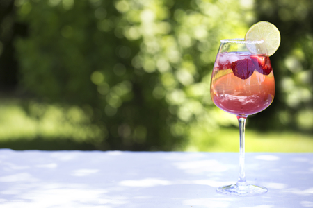 Homemade Summer Berry Drink. Lemonade with  strawberry with lime, mint in glass on table