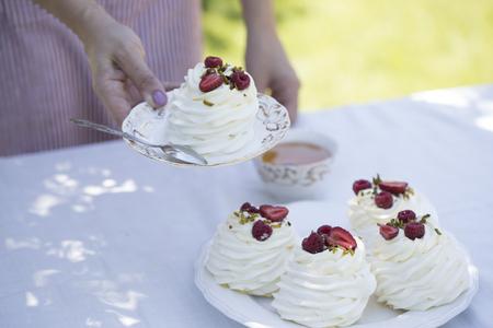 woman  holding pavlova cake. Pavlova cakes with cream and fresh summer berries