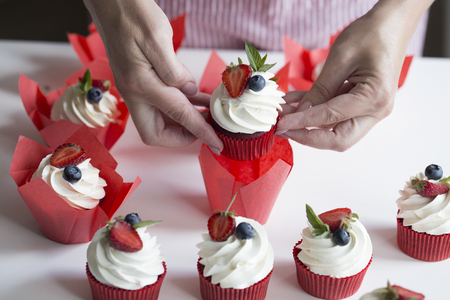 Closeup hands of chef decorating cupcakes with colored berries. Woman decorating a delicious cupcakes Stock Photo