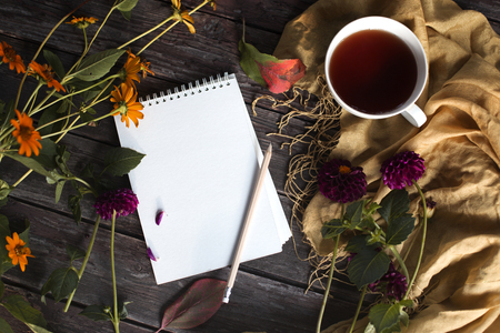 Autumn flatlay on wooden backdrop with a cup of tea and fallen dry yellow, red leaves, flowers. Free space for text. Cozy home concept
