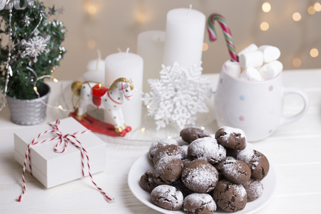 Chocolate brownie cookies in powdered sugar.chocolate cookies with christmas background. Chocolate Crinkle Cookies in powdered sugar and Christmas decoration