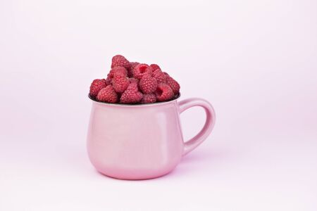 Enamel Mug with raspberries.  Pink Enamel cup with raspberries. fresh raspberry in enamel cup over pink background