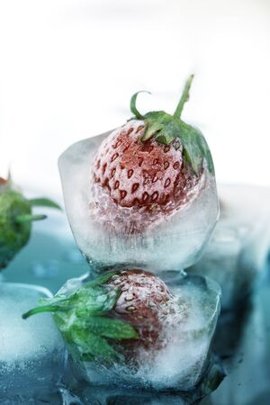 Ice cube and strawberry. Close up of strawberry frozen in ice