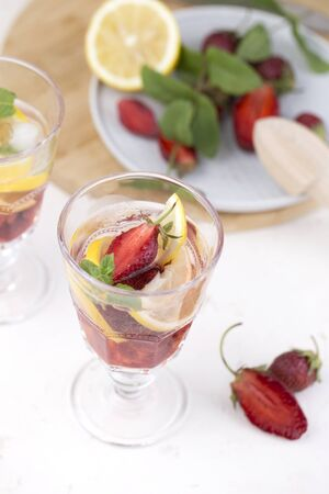 cold strawberry lemonade juice in the glasses with ice cubes. Summer refreshing drink. Cold detox water