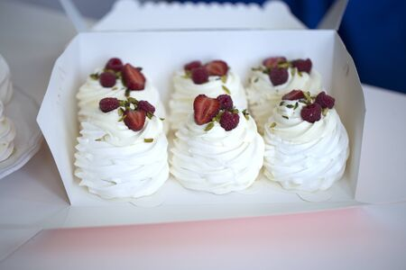 Pavlova cakes with cream and fresh summer berries. Pavlova cakes in a box. Close up view of a box full of mini meringue Pavlovas nests with cream, red fruits 版權商用圖片