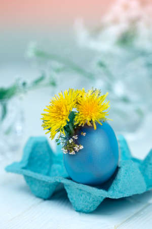 Spring religious holiday background.Easter egg, yellow dandelion flowers on a bright background