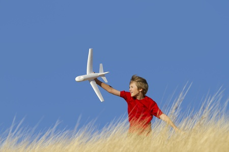 Young Boy Playing with Toy Glider Airplane in Grassy Field Stock Photo