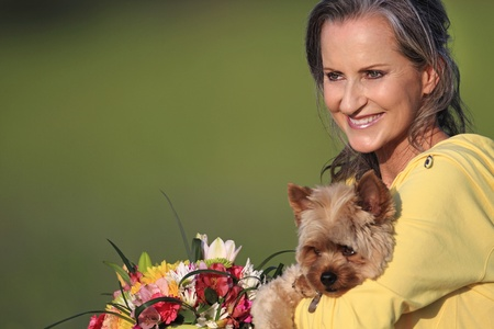 Closeup of older woman holding her pet Yorkshire Terrier. Stock Photo