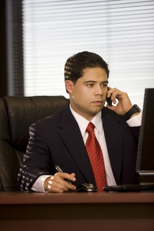 Handsome young man holding cellphone in the office. Stock Photo