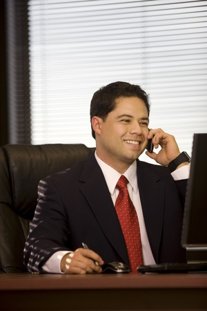 Young man in the office talking on cellphone. Stock Photo