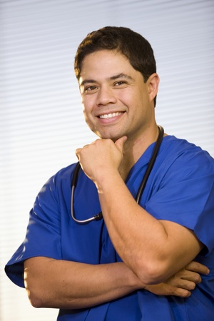 Young doctor wearing scrubs with  stethoscope around neck.