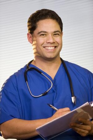 Young doctor wearing scrubs smilng for the camera.