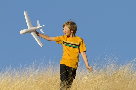 Caucasian male playing in field with toy airplane.