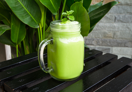 Green tea smoothies in glass on black wooden table.