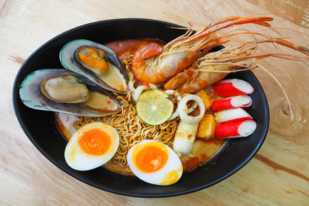 Noodles spicy shrimp soup in black bowl on wooden table Stock Photo
