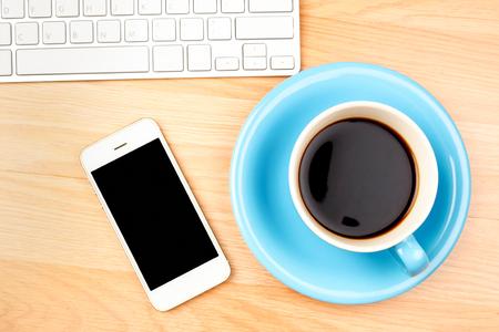 Taza de café azul y blanco y smartphone con pantalla en blanco sobre fondo de mesa de madera.