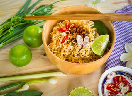 Instant noodles in wooden bowl and vegetable side dishes on wood background
