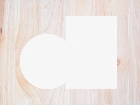 White circle paper and blank white paper on vintage brown wooden background. top view