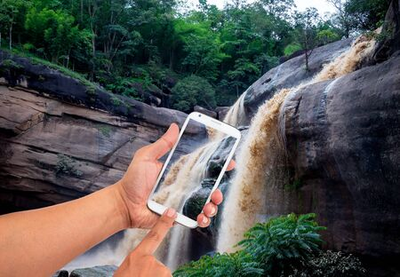 Man hand is holding a modern touch screen phone of waterfall in background