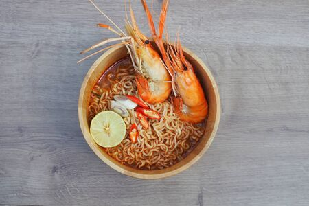 Spicy instant noodles soup with shrimp in wooden bowl on wood background,Tom yum kung