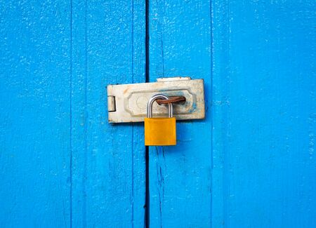 Locked padlock with chain at blue wooden door textured background