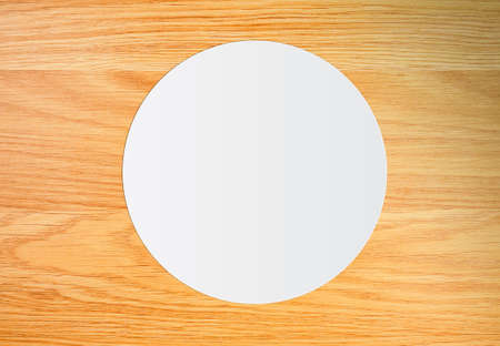 White circle paper on vintage brown wooden background. top view