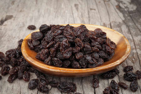 Organic dried Raisins in wood bowls on old wooden table background, Currant