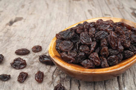 Organic dried Raisins in wood bowls on old wooden table, Currant