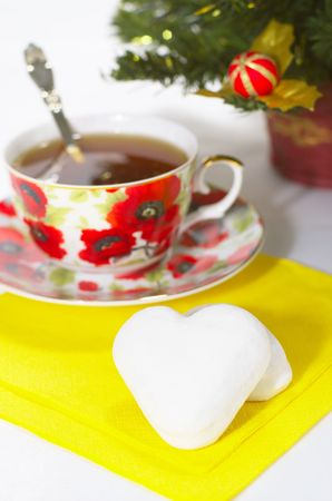 treacle: white treacle cake in form heart with cup of tea on background fir tree Stock Photo
