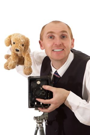 peers: photographer keeps toy smiles peers into eye and takes pictures old camera